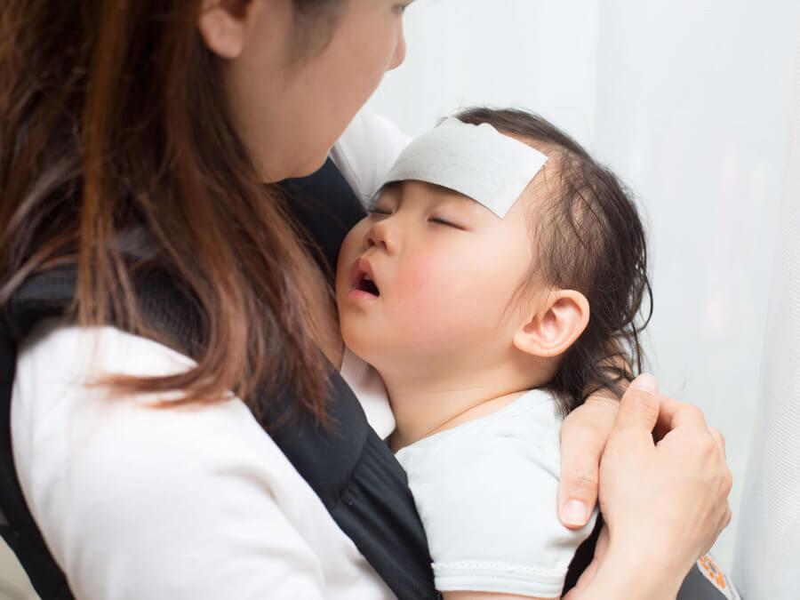 病気の子どもを心配そうに見つめる母